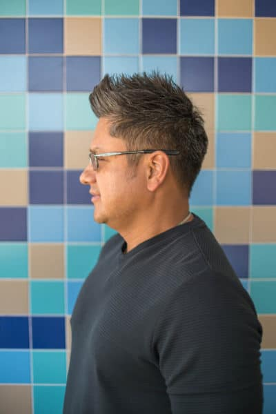 short hairstyle men posing at the hair salon with colorful tiles behind him